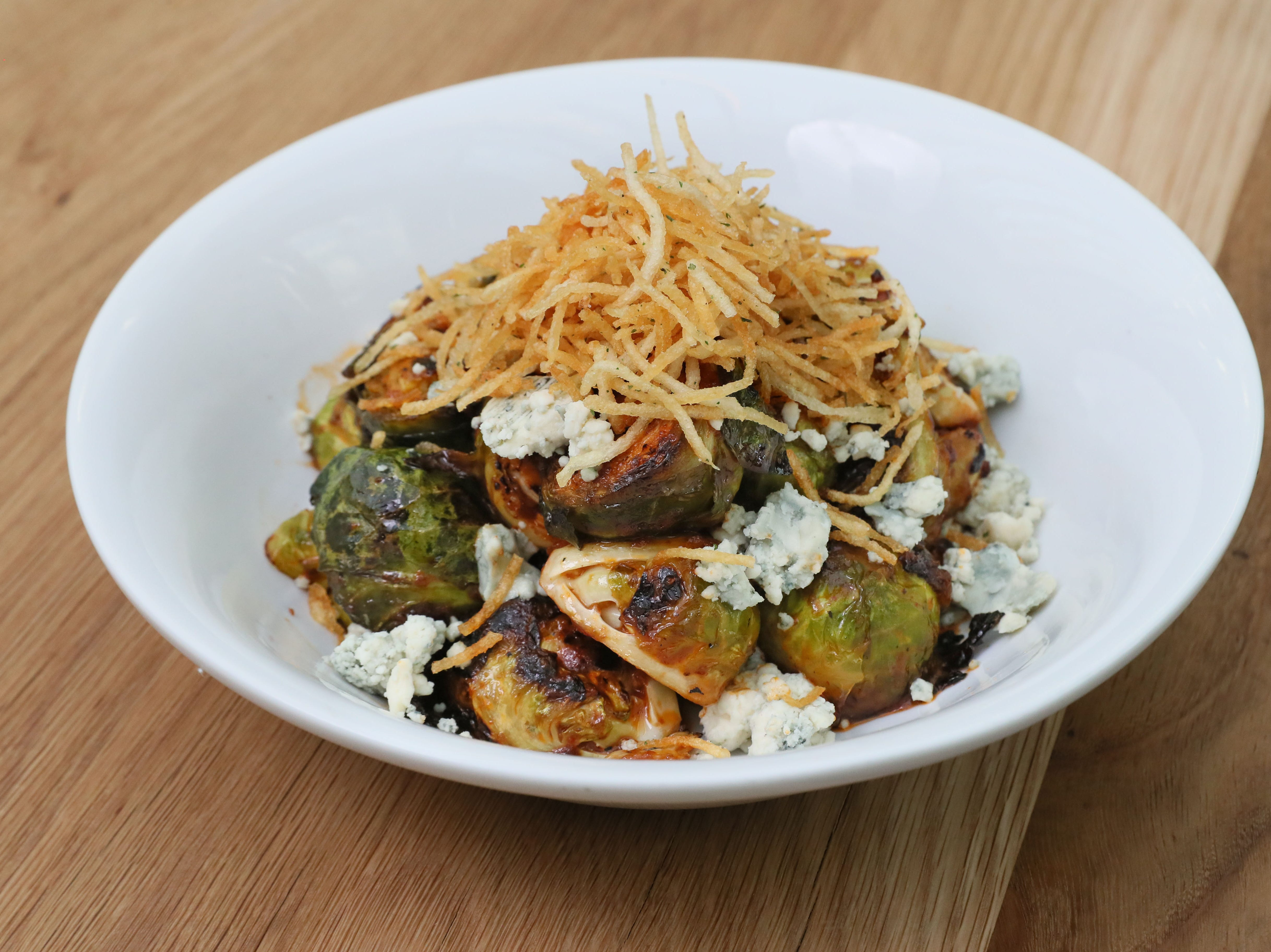 Brussels sprouts make a shareable snack when they're griddled and tossed in spicier-than-usual Buffalo sauce and topped with blue cheese and crunchy shoestring potatoes at Glass + Griddle.