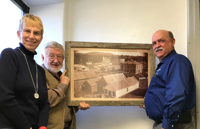Jennifer Baker (from left), Vice President, and David Benedict,President of the Baxter County Historical and Genealogical Society, recently presented ahistoric reprint to County Judge Mickey Pendegrass, to be displayed in the third-floor stairwell at the Baxter County Courthouse.The reprint depicts the Mountain Home square taken circa1895, from the perspective looking northwest.It is the earliest known photo of the MountainHome square. The frame for the picture was handmade by David Benedict, using old lumber from the smokehouse behind the Leonard home that was torn down on South College several years ago.