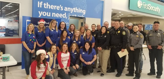Junior Auxiliary members and local law enforcement officers are pictured at the annual Shop With a Cop campaign for children on Dec. 1 at Walmart. Junior Auxiliary conducted its Food for Families program to provide a holiday meal to the families of children who participated in Shop with a Cop.