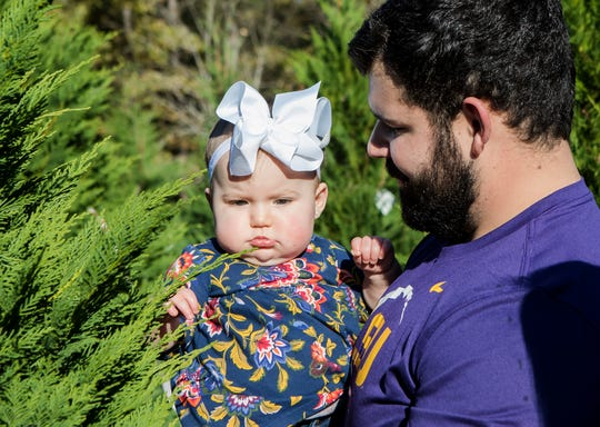 """Matt Fontenot lets his daughter, Larkin, 9 months, touch a potential family Christmas tree while shopping for a tree at Precious Memories Christmas Tree farm in Calhoun, La. on Nov. 17. """"I grew up and that was kind of the big family tradition, picking a tree together,"""" Matt said about bringing his daughter out to the tree farm. """"That's what we wanted her to do."""""""
