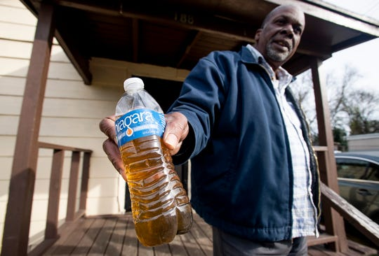 Willie Thomas, Jr., shows a sample of his tap water at his home in the Newtown neighborhood in Montgomery, Ala., on Wednesday December 12, 2018.