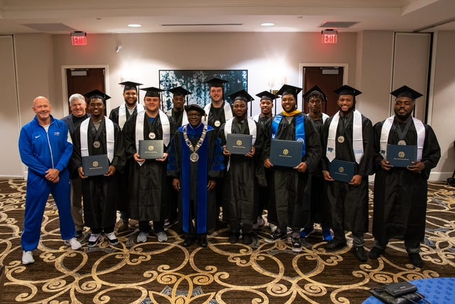 MTSU football players in their graduation regalia with president Sidney McPhee and coach Rick Stockstill and athletic director Chris Massaro.