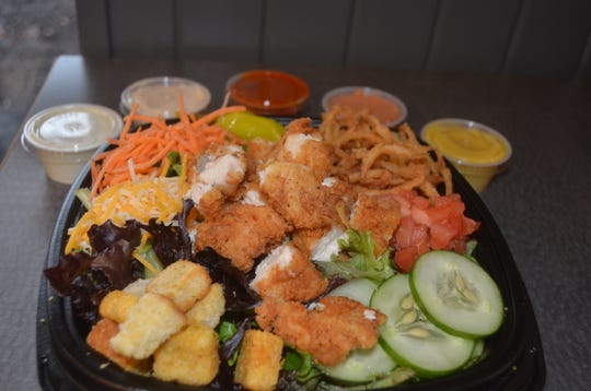 The Slim Salad features chicken tenders, cheese, tomatoes, cucumbers, fried onions, carrots and croutons at Slim Chickens in Hendersonville.