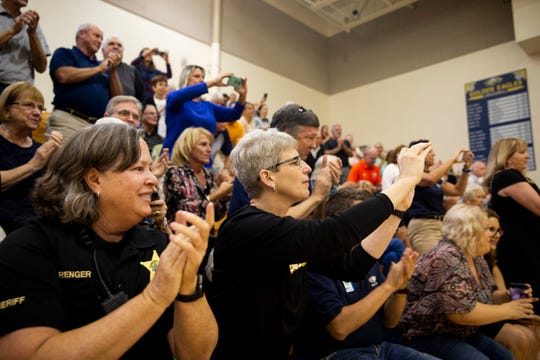 Audience members clap and take photos during the dedication of the Coach Dave Walker Court on Thursday, December 13, 2018, at Naples High School.