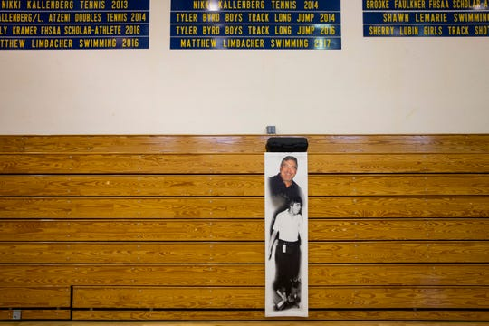 Photos of Dave Walker hang from the bleachers during the dedication of the Coach Dave Walker Court on Thursday, December 13, 2018, at Naples High School.