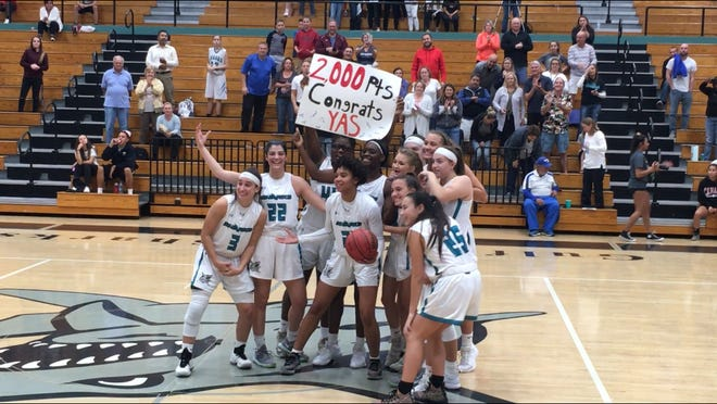 Gulf Coast High School senior basketball player Yasmeen Chang, center, poses with her teammates after scoring her 2,000th career point on Wednesday.