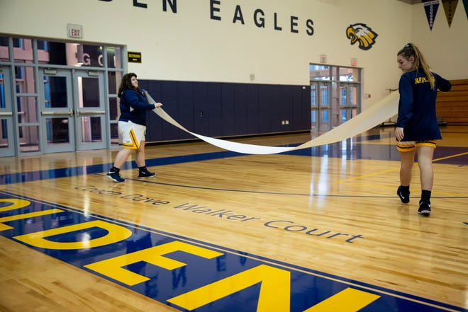 Members of the Naples High School girls basketball team unveil the new name on the hardwood during the dedication of the Coach Dave Walker Court on Thursday, December 13, 2018, at Naples High School.