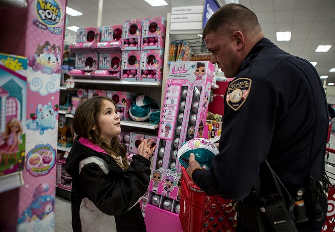 """Chloe Harrison, 8, of Pataskala explains to Officer Leland Kelly of New Albany what the toy she picked out was. Harrison was one of 25 kids selected to """"shop with a cop"""" Wednesday night in Pataskala. Each year the Pataskala Police Department selects around 25 kids in need to go shopping with are police officers at target. They children are each paired with a cop and get to pick out their own toys for Christmas."""