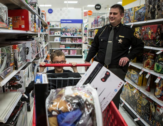"""Gavin Bates, 7, of Pataskala pushes his cart of toys in front of Licking County Sheriff, Tony Kolas. Bates was one of 25 kids selected to """"shop with a cop"""" Wednesday night in Pataskala. Each year the Pataskala Police Department selects around 25 kids in need to go shopping with are police officers at target. They children are each paired with a cop and get to pick out their own toys for Christmas."""