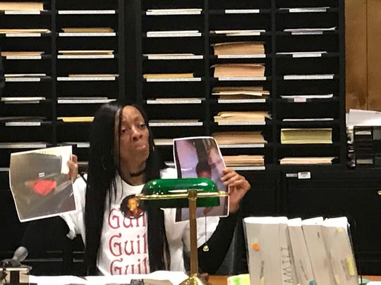 Naomi Fields holds a picture of her son, JaQuill lying in a casket during sentencing on Thursday.