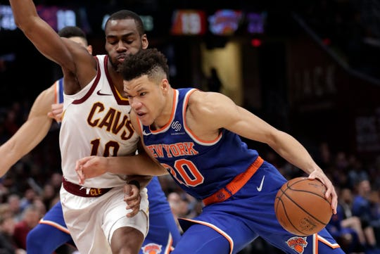 New York Knicks' Kevin Knox (20) drives past Cleveland Cavaliers' Alec Burks (10) in the second half of an NBA basketball game, Wednesday, Dec. 12, 2018, in Cleveland. The Cavaliers won 113-106.