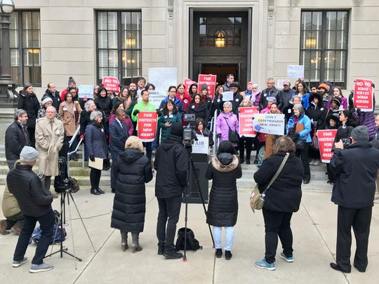 Dozens of progressive activists, academics and good-government advocates gathered on the Statehouse steps to speak against a controversial redistricting proposal on Dec. 13, 2018.