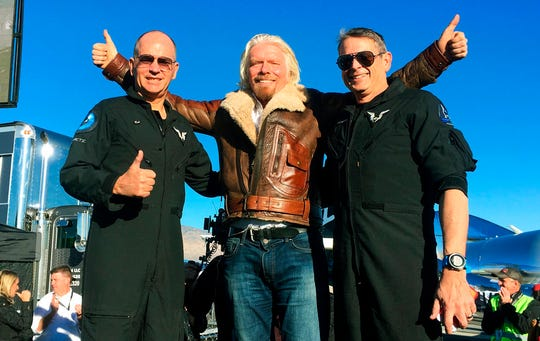 """Richard Branson, center, celebrates with pilots Rick """"CJ"""" Sturckow, left, and Mark """"Forger"""" Stucky, right, after Virgin Galactic's tourism spaceship climbed more than 50 miles high above California's Mojave Desert on Thursday, Dec. 13, 2018."""