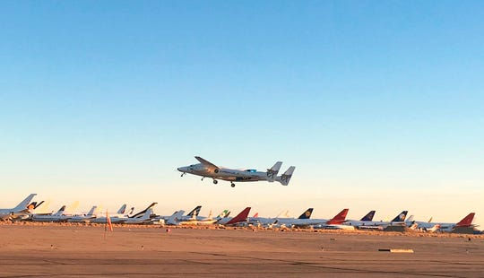 A jet carrying Virgin Galactic's tourism spaceship takes off from Mojave Air and Space Port on Thursday, Dec. 13, 2018 in Mojave, Calif.