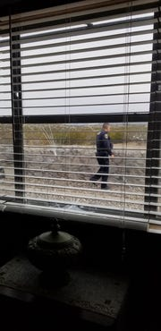 A Las Cruces police officer collects evidence from a home on Dyer Street on Tuesday. The resident of the home claims someone who tried to break in left behind human fecal matter and blood.