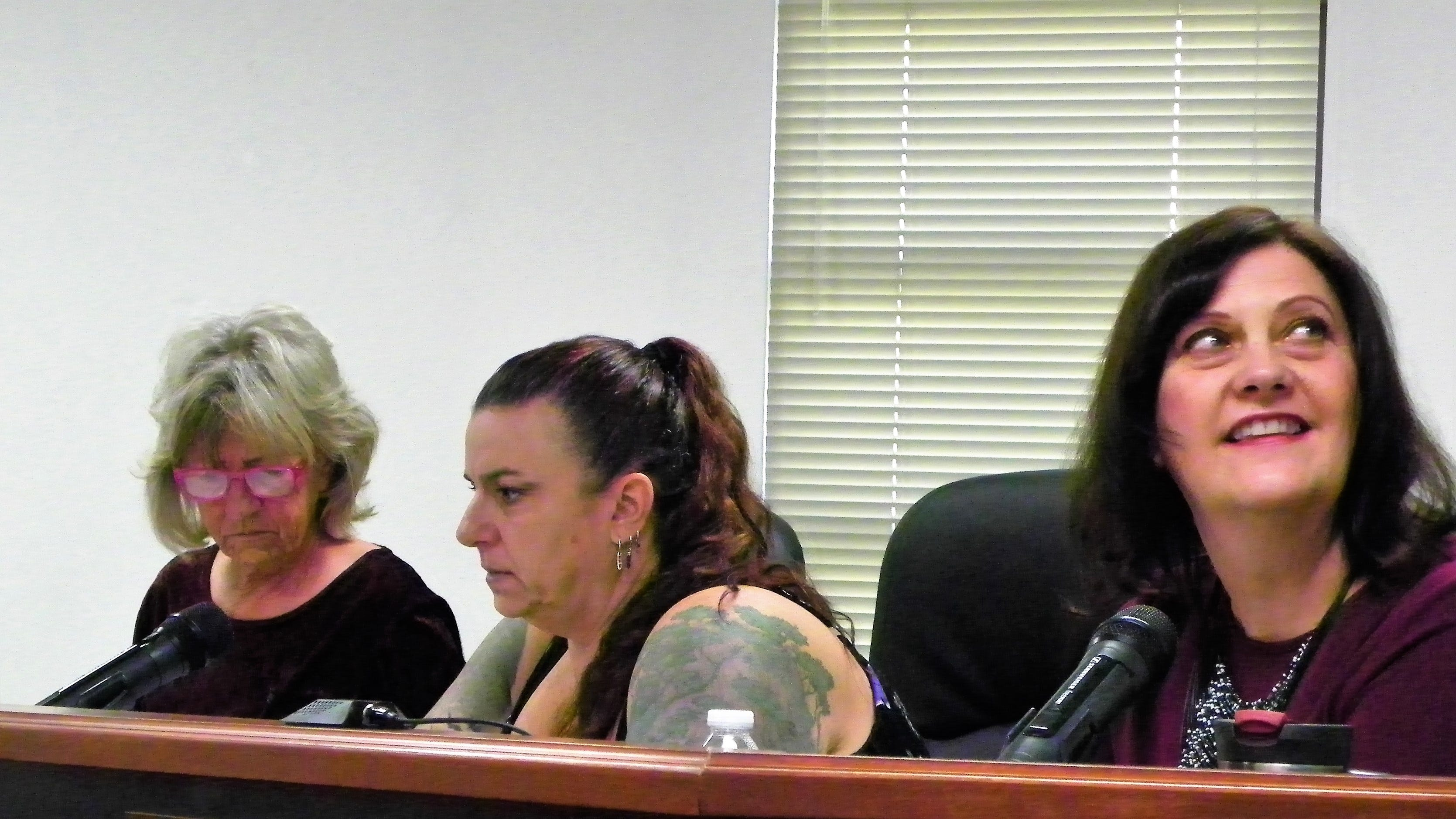 Otero County Vice-Chairwoman Susan Flores, right, looks at one of the flag mock-ups on the big monitor in the Otero County Commission Chambers Thursday while Otero County Commissioner Janet White, left and Otero County Commission Chairwoman Lori Bies look at Zia symbol possibilities.