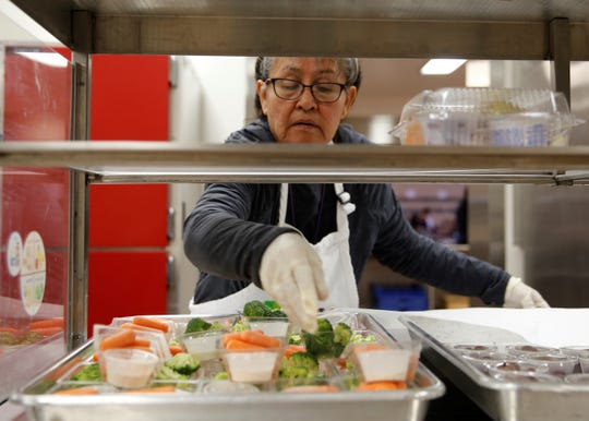 Kitchen Manager Triva Esplain resupplies carrot and broccoli trays on Wednesday at Eva B. Stokely Elementary School in Shiprock.