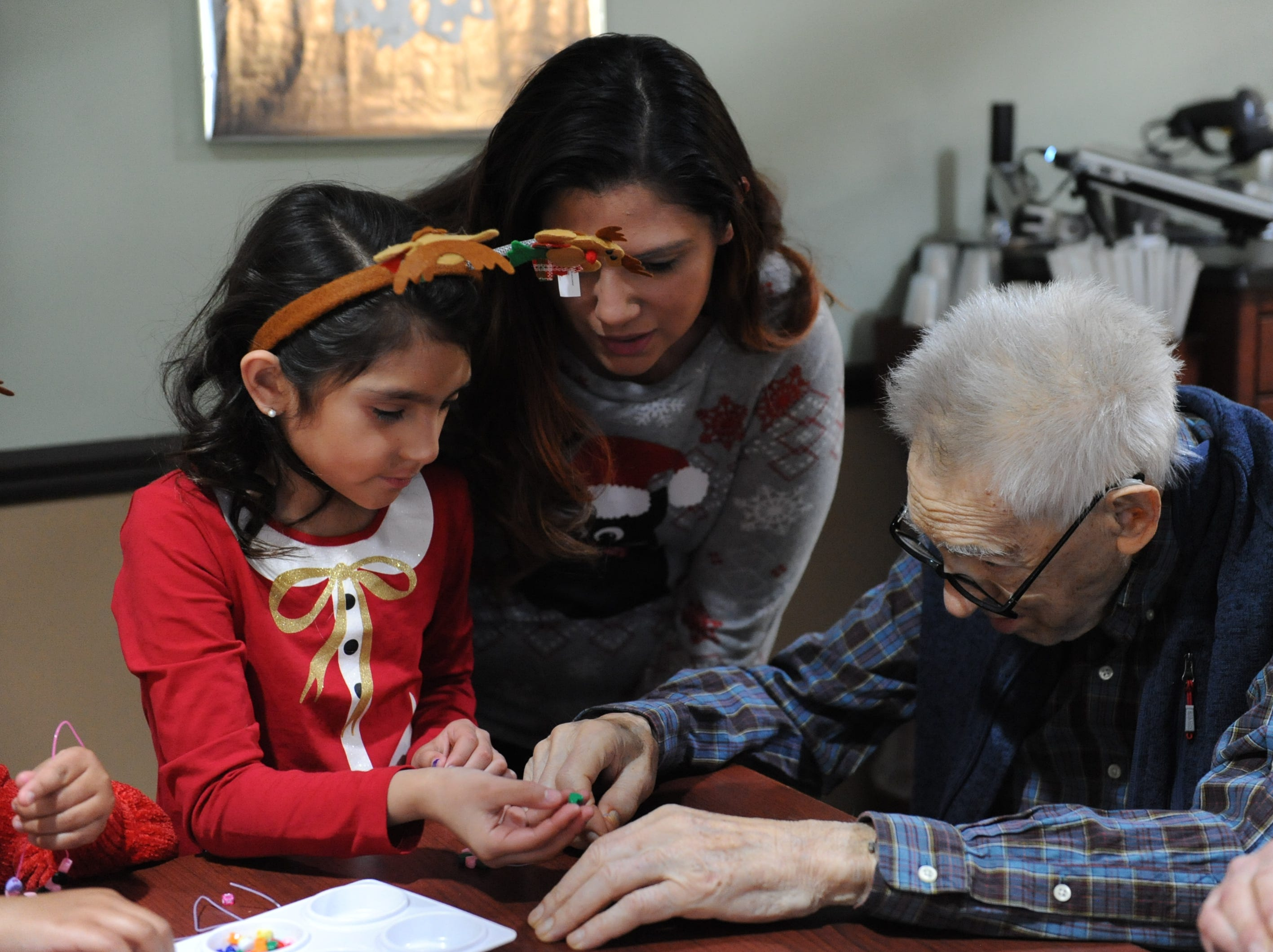 Bianca Mendoza and daughter Maia help Dr. Joel Silver with crafts at Courtyard Manor.