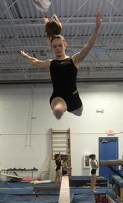 Freshman Maeve Wright practices her balance beam routine at the Gymnastics Training Center.