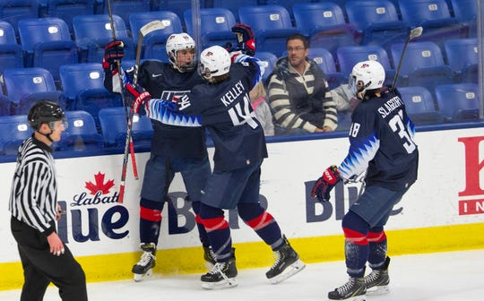 Connor Kelley (44) and Landon Slaggert (38) congratulate Jacob Truscott (left) after Truscott scored to break a 1-1 tie in the second period. It proved to be the winning goal in a 3 -1 victory against Team Switzerland.