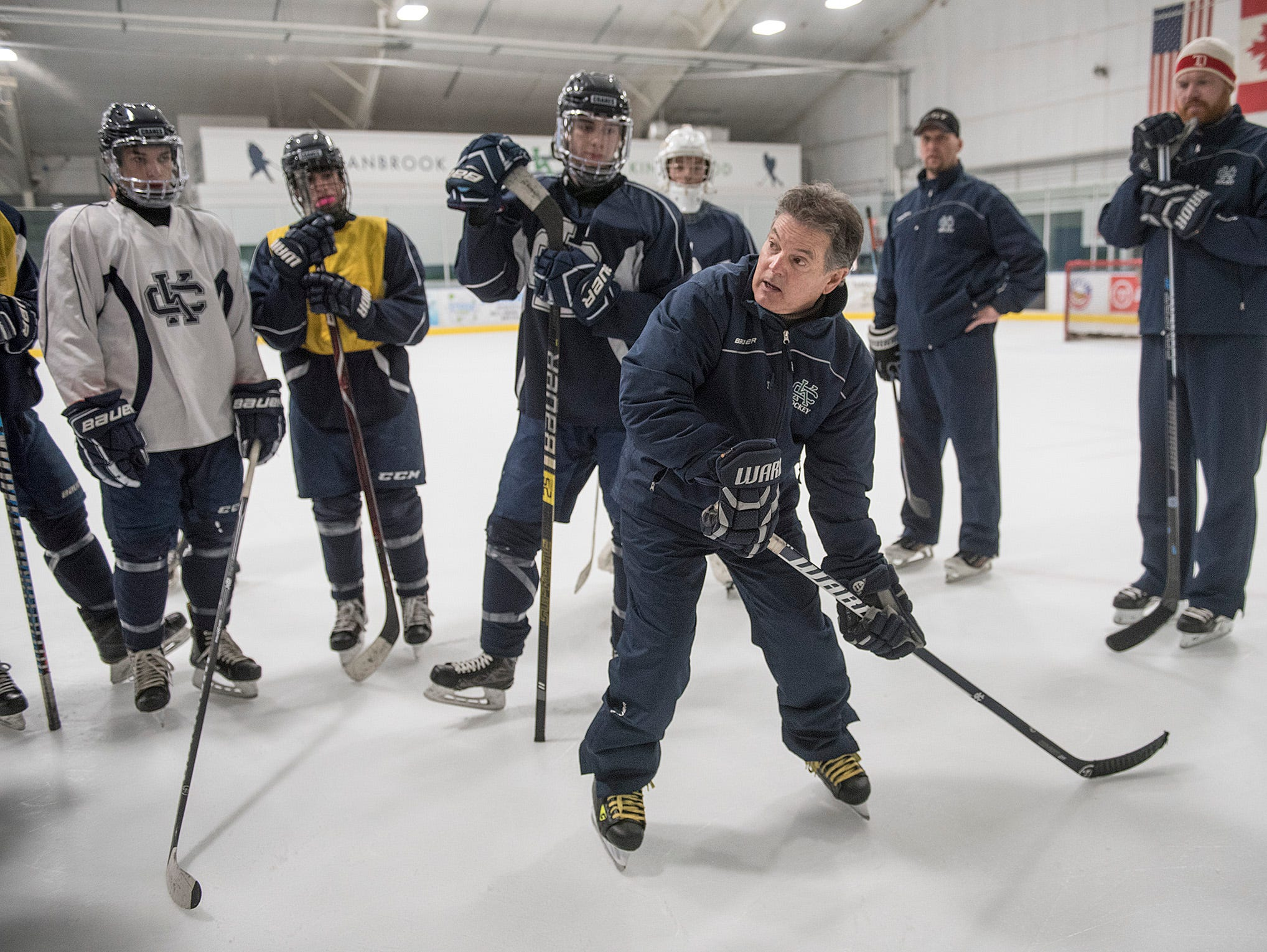 Cranbrook Hockey Coach Andy Weidenbach works with players during practice.