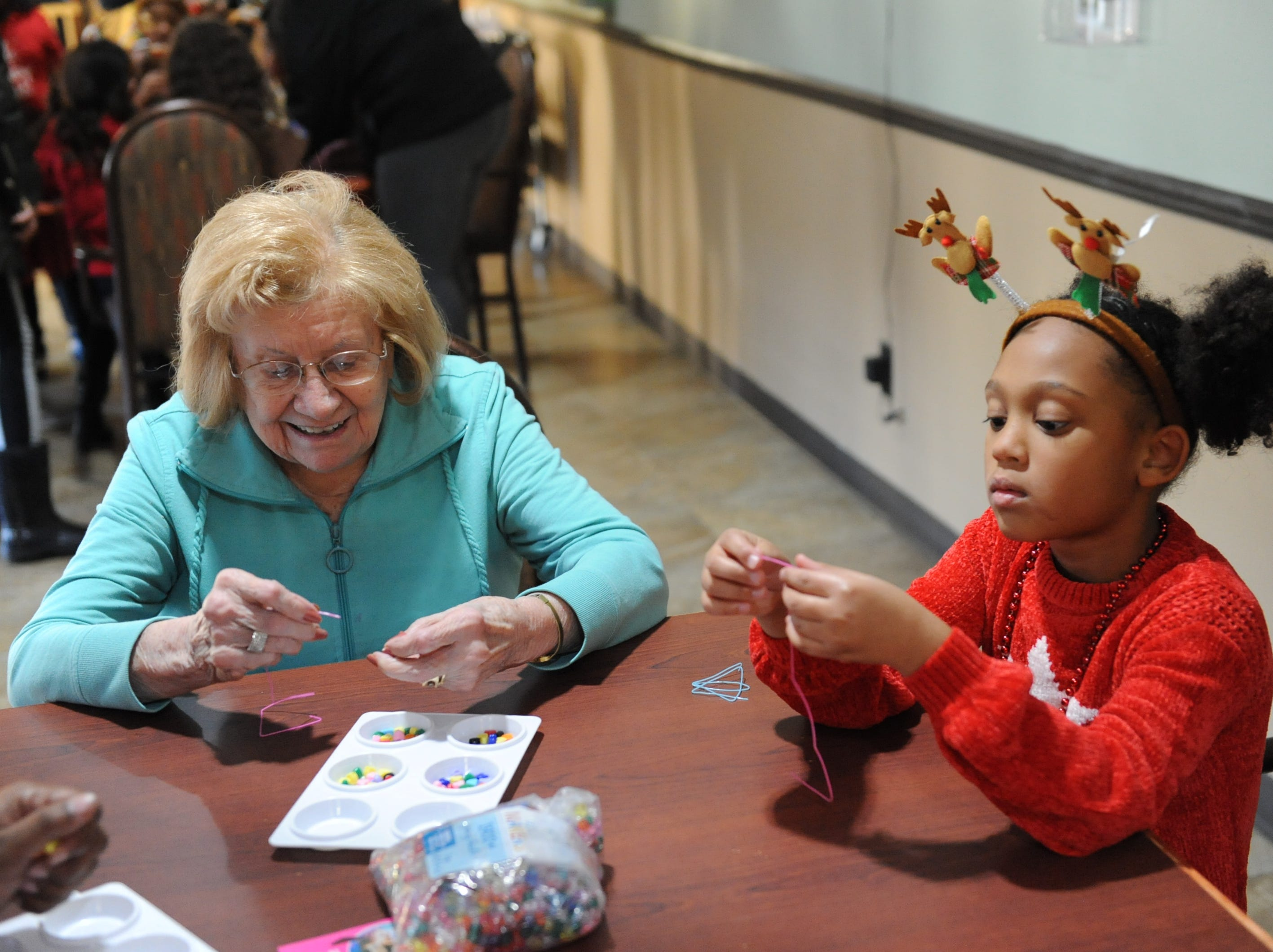 Verna Kubaba gets help making a bracelet from Brownie Tamsim Palland during a visit Dec. 8.