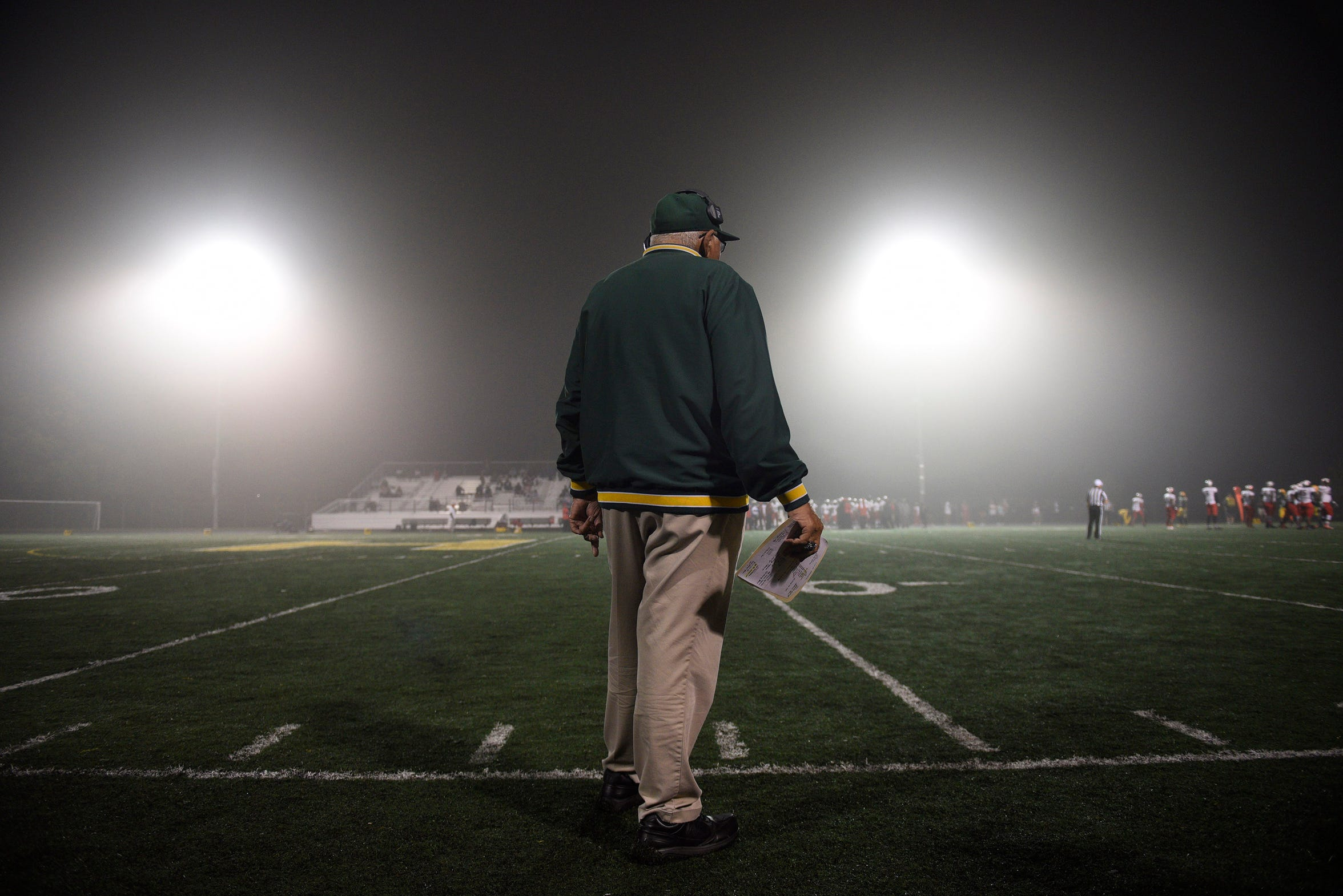 John Herrington on the foggy sidelines Oct. 6, 2017 moments before the end of the game against Oak Park won by the Hawks 17-14. The win gave Herrington 431 career victories tying him at the time with former Brother Rice Coach Al Fracassa for most victories.