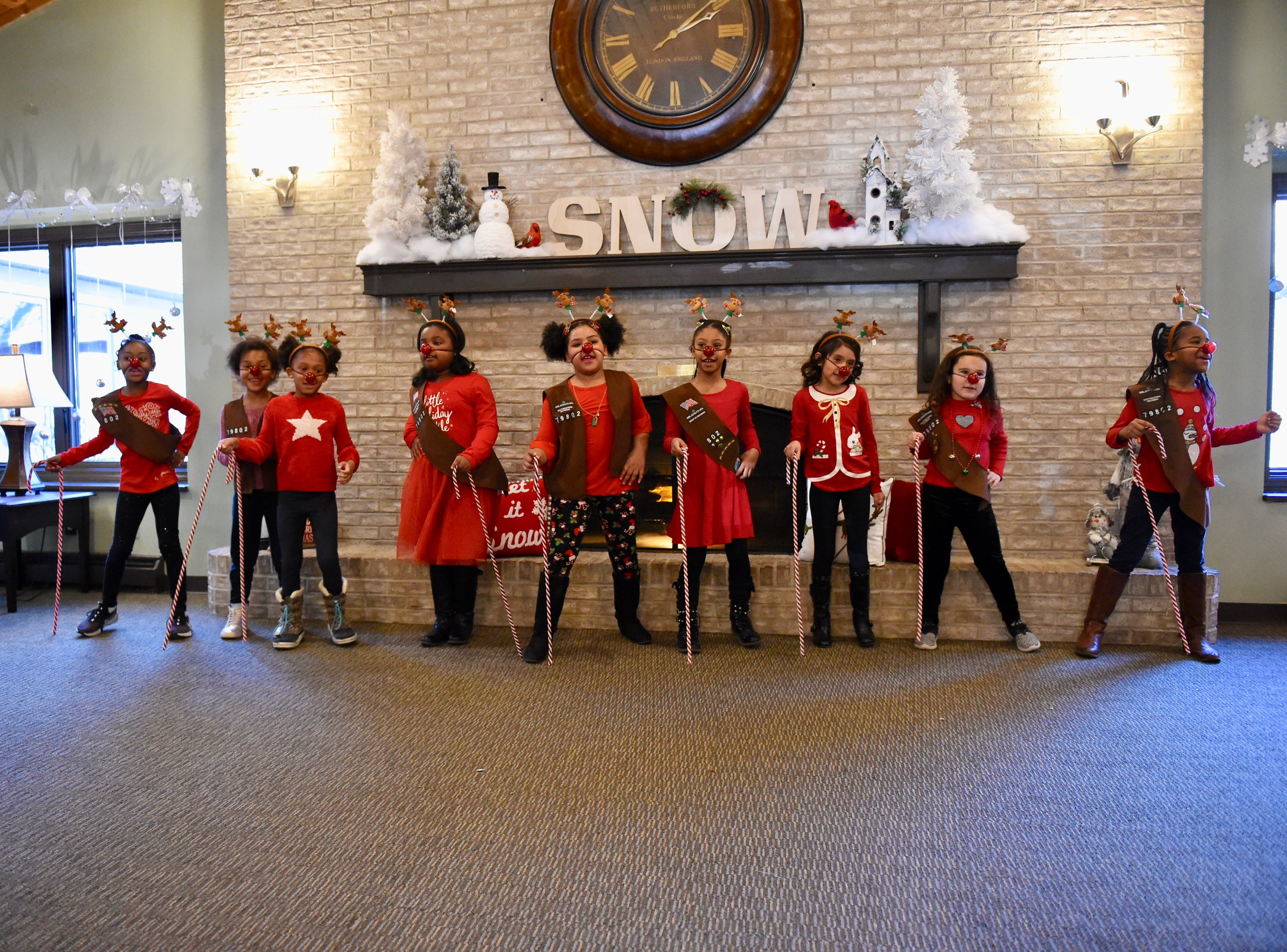 Wood Creek Elementary Brownie Troop # 79802 members Taelor Dowdell (from left), Lucy Deason, Tamsin Palland, Sanyia Dunlap, Daisy Thomas, Milani Parker, Mia Botello, Marissa Hochberg and Oliveah Taylor perform at Courtyard Manor of Farmington Hills on Saturday.