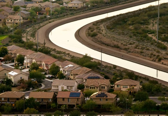The CAP Canal winds through a neighborhood in Phoenix as seen from the Deem Hills Recreation Area on December 12, 2018.