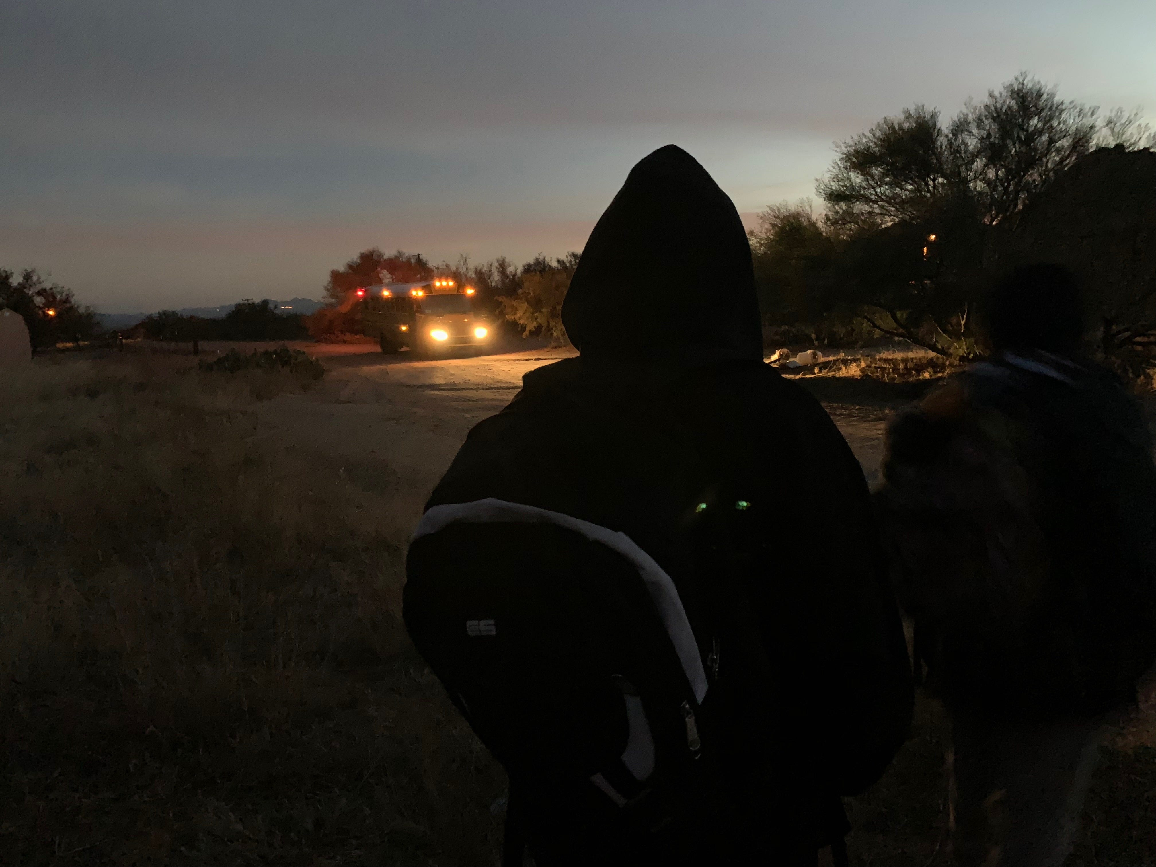 Two students from the Baboquivari Unified School District watch as their bus approaches in the early morning.