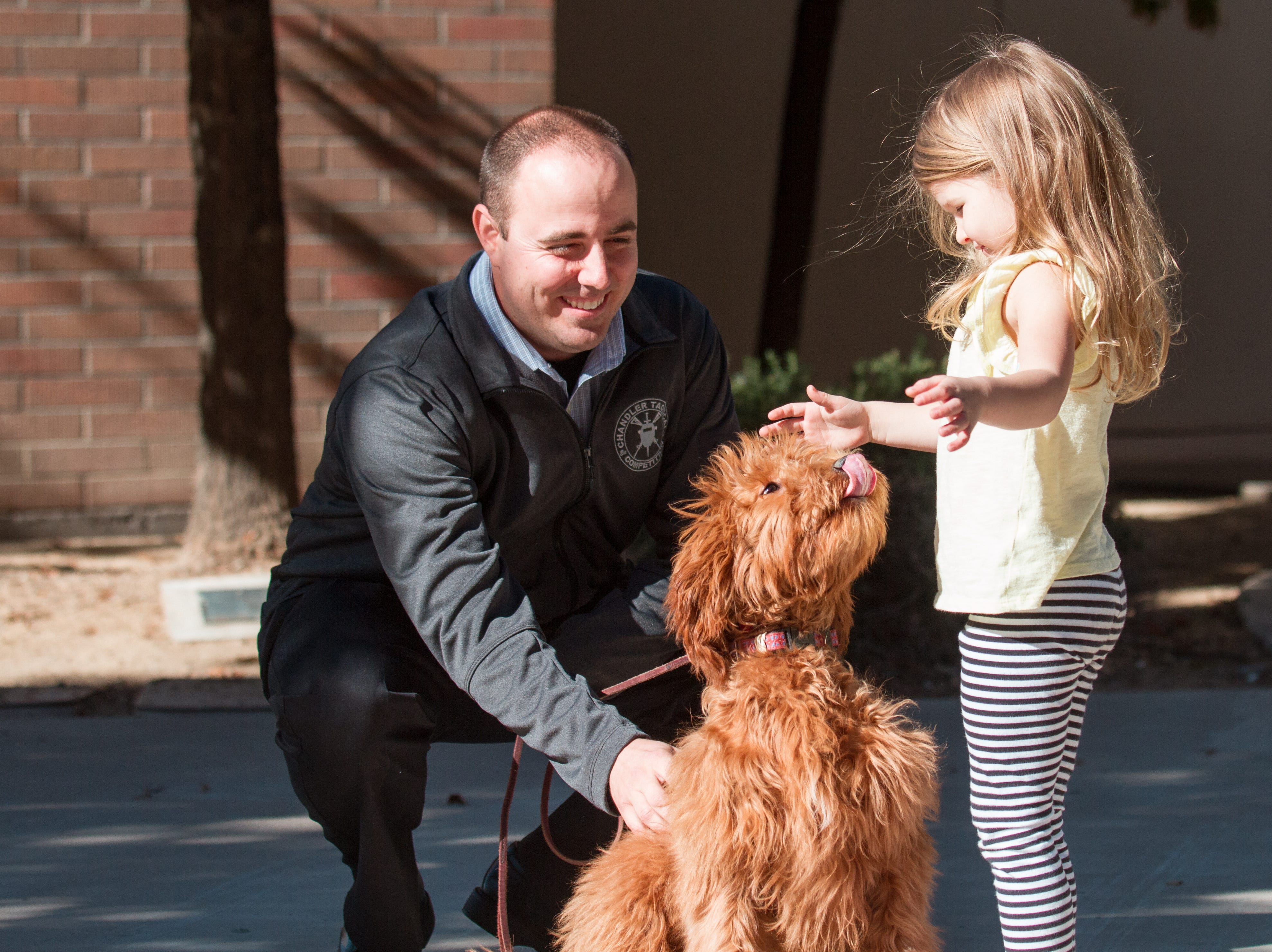 Chandler Police Department's new therapy dog, Annie, sits with Olivia Williams and her handler, Detective Brian Wagner, at the Chandler Police headquarters Dec. 13, 2018.