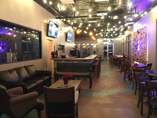 This interior photo of Desert Monks Brewing Co. shows the brewing room, comfortable seating, the bar and tables.