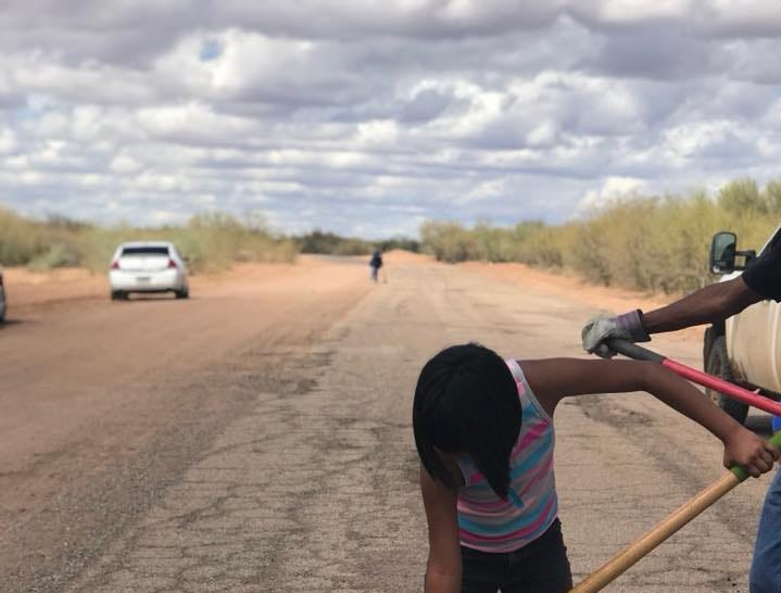 A student from the Baboquivari Unified School District patches up a hole on the road to Cowlic, a village on the Tohono O'odham reservation, earlier this year.