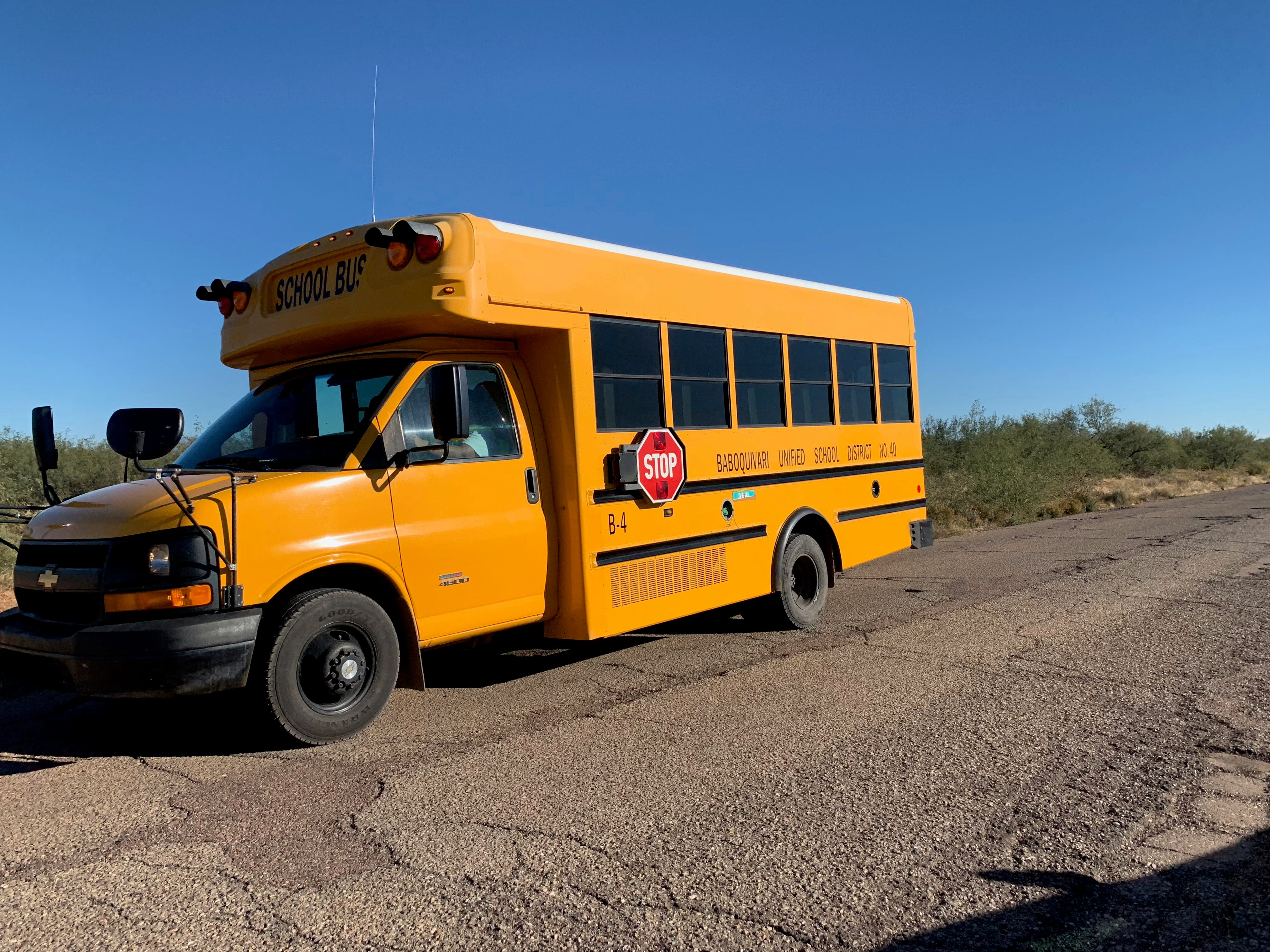 A school bus drives down a road to a village on the Tohono O'odham reservation in southern Arizona. The roads around villages experience extensive damage from flooding after rain.