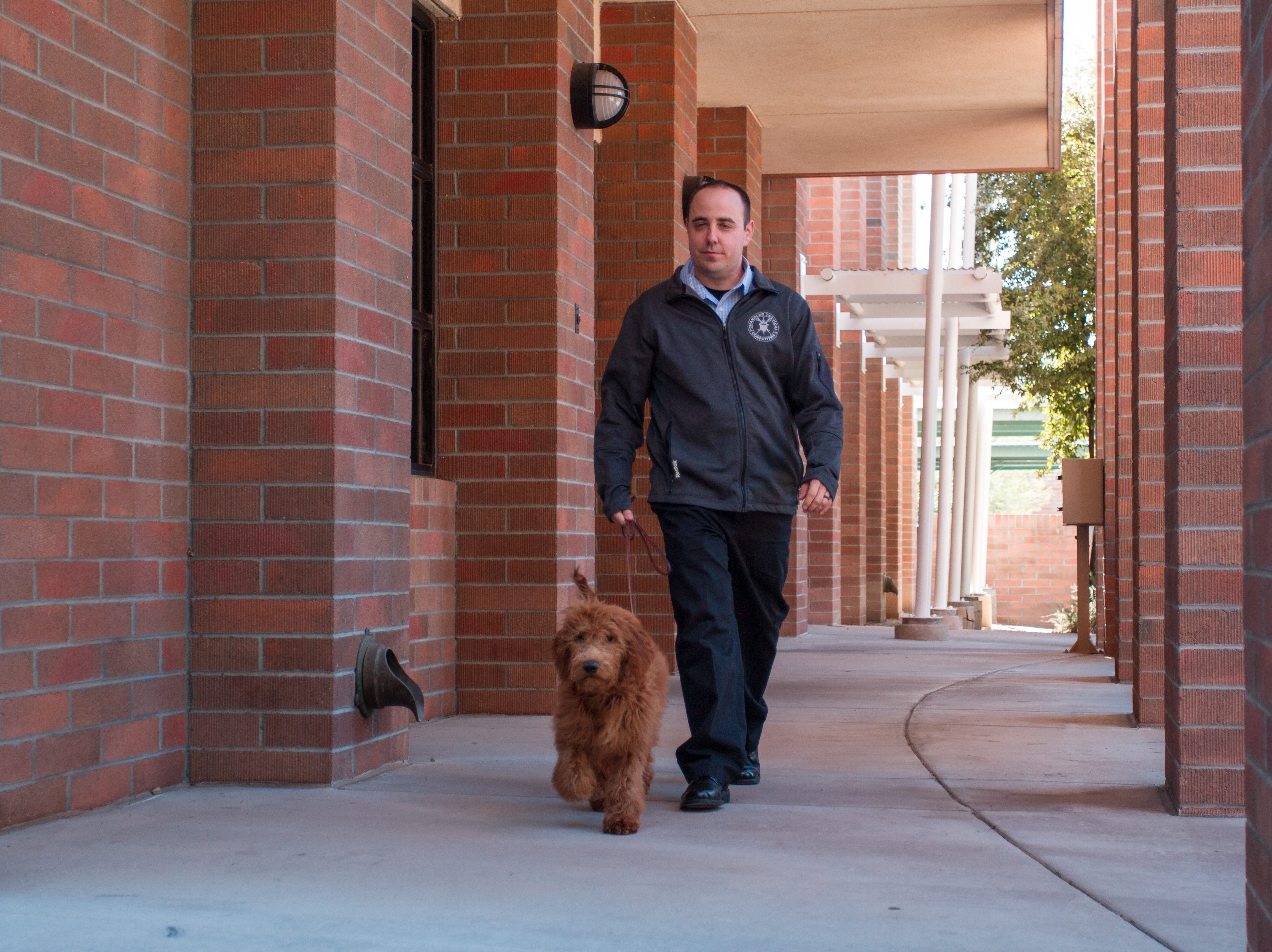 Chandler Police Department's new therapy dog, Annie, walks with her handler, Detective Brian Wagner, at the Chandler police headquarters Dec. 13, 2018.