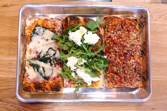 Pizza Margherita with tomato, fresh mozzarella and basil (left), pizza caprese with tomato, fresh mozzarella and arugula (center) and pizza Amatriciana with tomato, pancetta, onion and pecorino Romano (right) at Piazza Romana in Avondale.