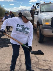 An employee of the Baboquivari Unified School District patches up a hole on the road to Cowlic, a village on the Tohono O'odham reservation, earlier this year.