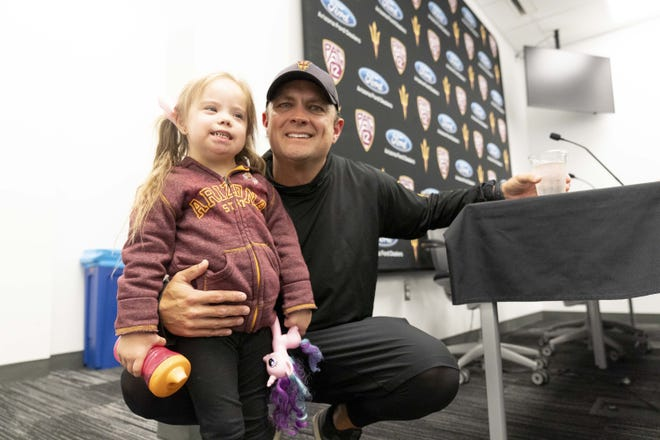 ASU defensive coordinator Danny Gonzales poses with his four-year-old daughter Abby during a news conference.