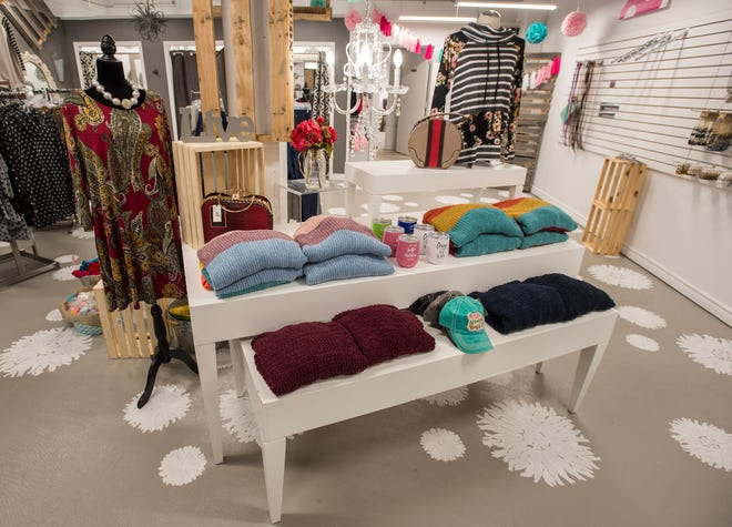 Clothing items and other accessories decorate a table inside Papaya Branch Boutique's newly added space.