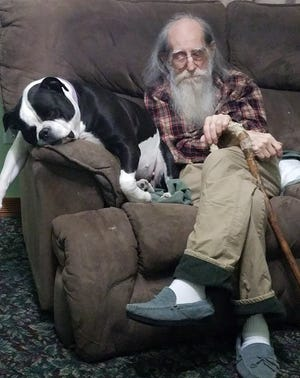 Joseph Humphries sits with the house dog, Layla, in a Port Huron home.
