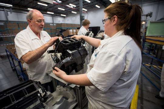 Samantha Rapley, right, and Randy Lowery work on an automotive HVAC assembly at Keihin Michigan Manufacturing LLC in Capac in this 2018 file photo.