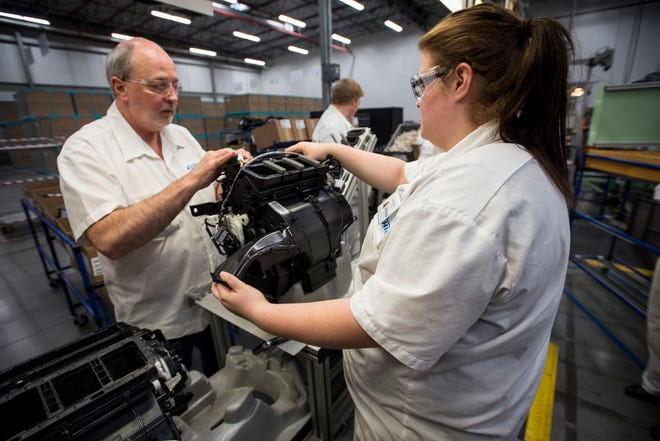 Randy Lowery and Samantha Rapley work on an automotive HVAC assembly Thursday, Dec. 13, 2018 at Keihin Michigan Manufacturing LLC in Capac.