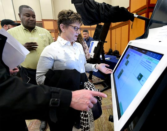 Paula Sembach of Dauphin County is advised by Willie Wesley, Jr, director of business development for Election Systems and Software, while sampling a voting machine with her husband Fred, who is chief of staff to State Senator Mike Folmer Wednesday, Dec. 12, 2018. They were attending the New Voting Systems Expo hosted by the Pennsylvania Department of State at Dickinson College. Pennsylvania counties are preparing to replace voting machines after Gov. Tom Wolf in April mandated that voting machines used in the state have a verifiable paper trail. Bill Kalina photo