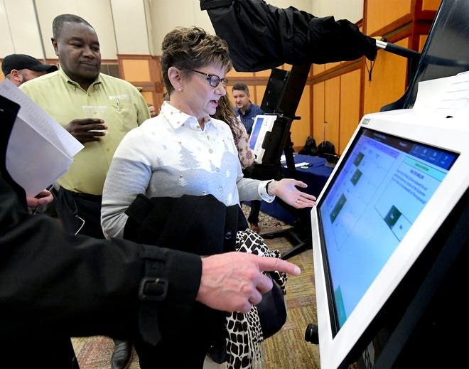 Paula Sembach of Dauphin County is advised by Willie Wesley, Jr, director of business development for Election Systems and Software, while sampling a voting machine with her husband Fred, who is chief of staff to State Senator Mike Folmer Wednesday, Dec. 12, 2018. They were attending the New Voting Systems Expo hosted by the Pennsylvania Department of State at Dickinson College. Pennsylvania counties are preparing to replace voting machinesafterGov. Tom Wolf in April mandatedthat voting machines used in the state have a verifiable paper trail. Bill Kalina photo