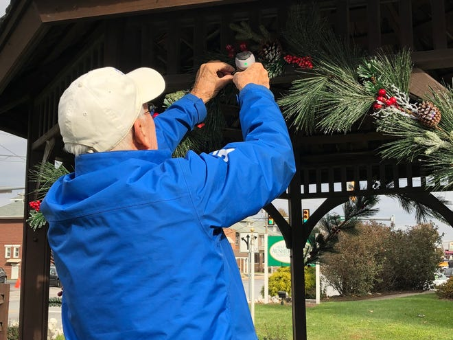 Bob Etzweiler, funeral director of Etzweiler Family Funeral Service, hangs greens on the Giving Gazebo in West York. Winter warmth items like hats and gloves are going to be stored in totes under the gazebo at 2000 West Market St., through Dec. 23. Anyone in need is welcome to take items.