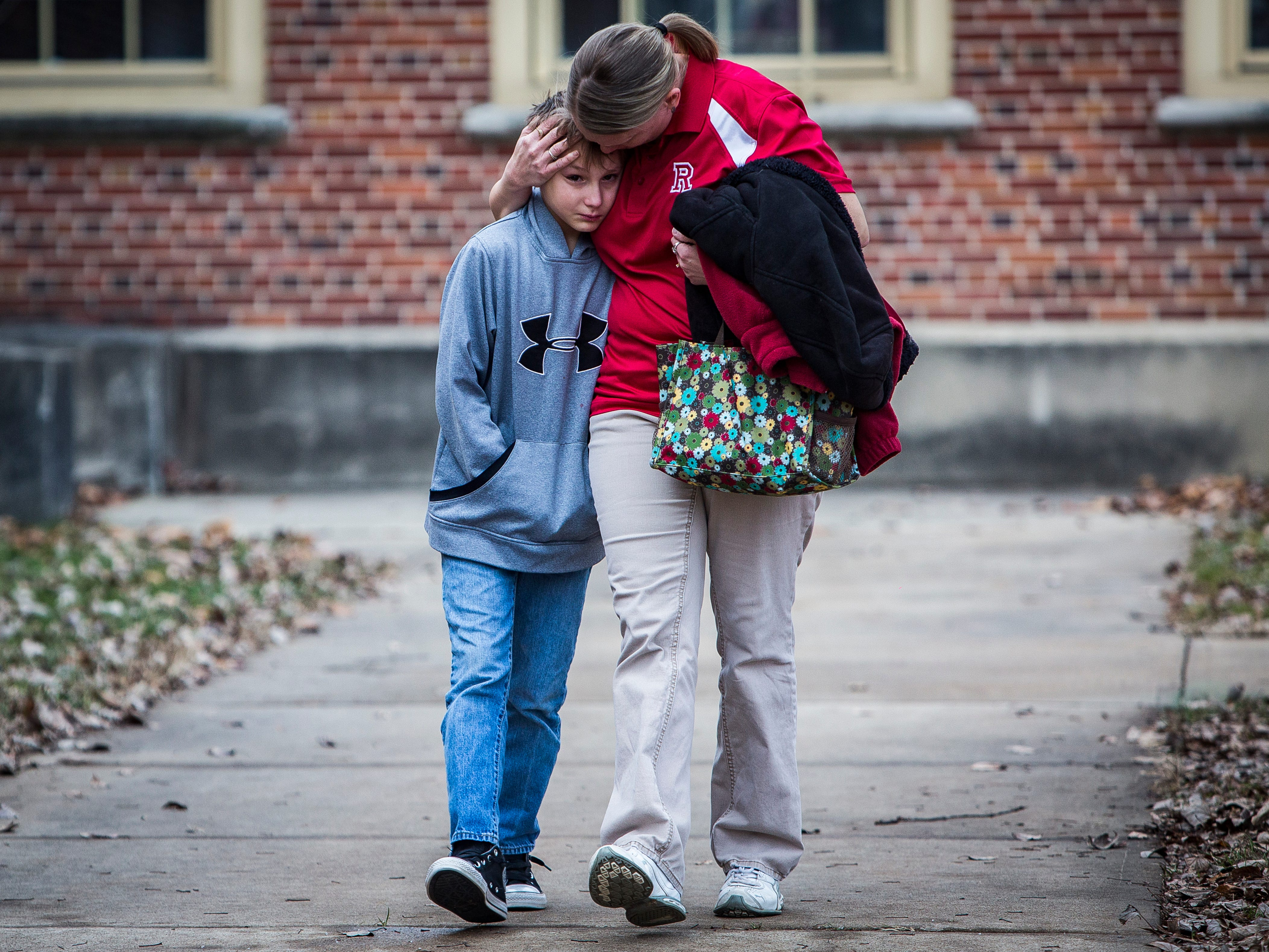 Marietta Bryant hugs her son, Austin, after they reunited at the Civic Performing Arts Center following an attempted school shooting at Dennis Middle School Thursday morning.