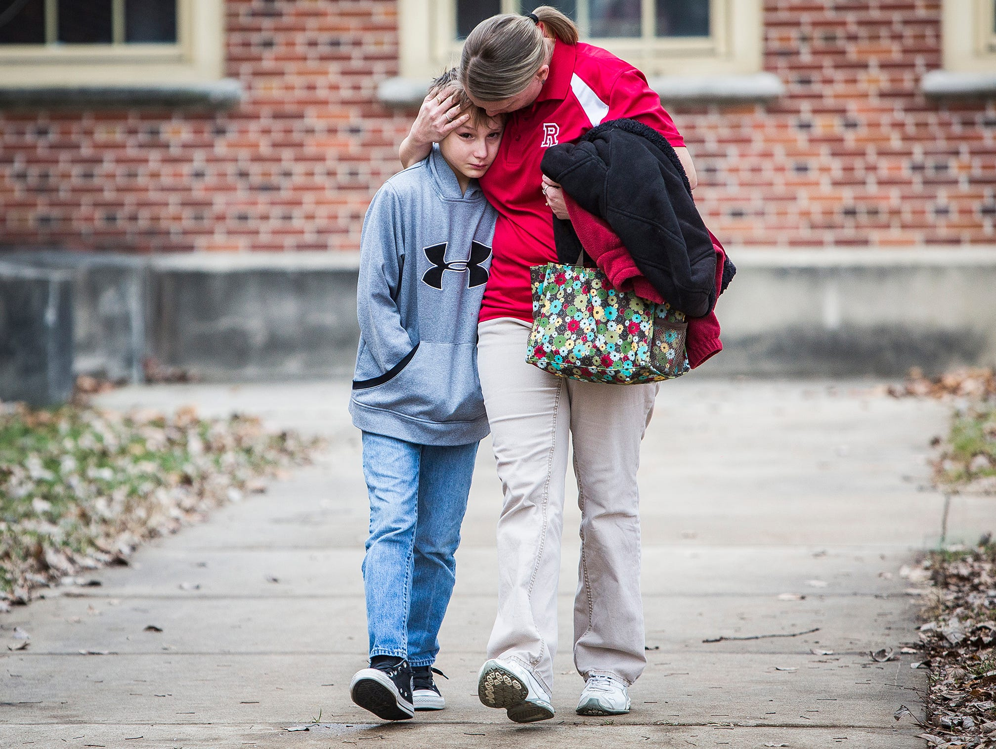 Marietta Bryant exits the Civic Hall Performing Arts Center after reuniting with her son, Austin, following a shooting that occurred at Dennis Intermediate School Thursday morning.