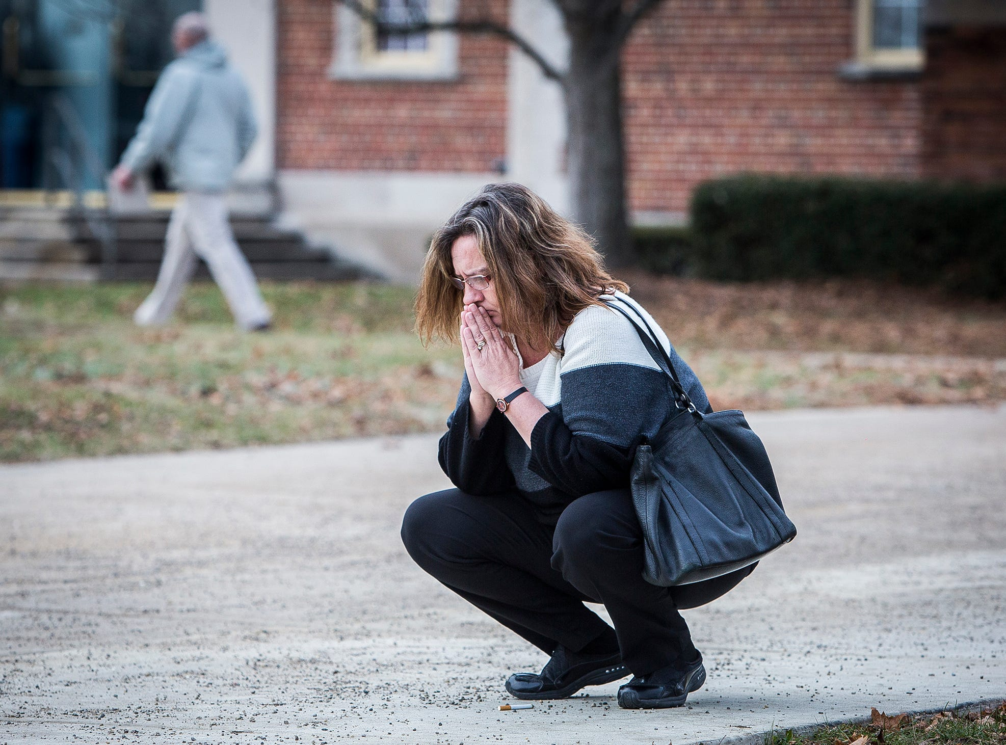 A parent prays outside of the Civic Hall Performing Arts Center before going inside to reunite with her child after a shooting occurred at Dennis Intermediate School in Richmond Thursday morning.