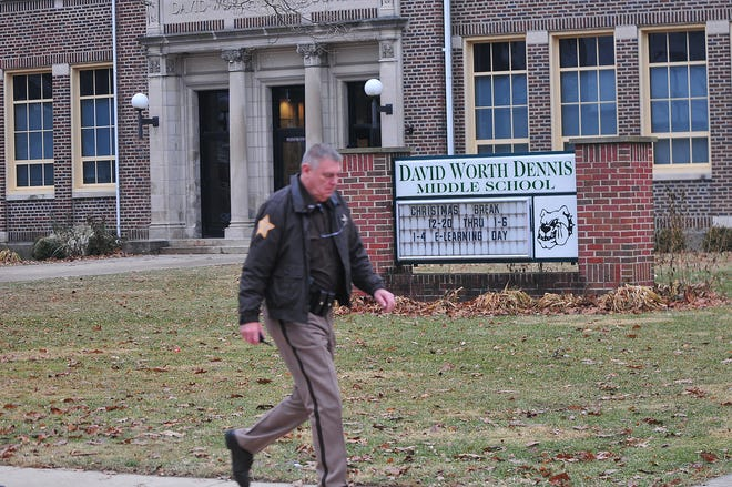 An officer walks outside Dennis Intermediate School after police exchanged gunfire with a suspect near Dennis the morning of Dec. 13, 2018.