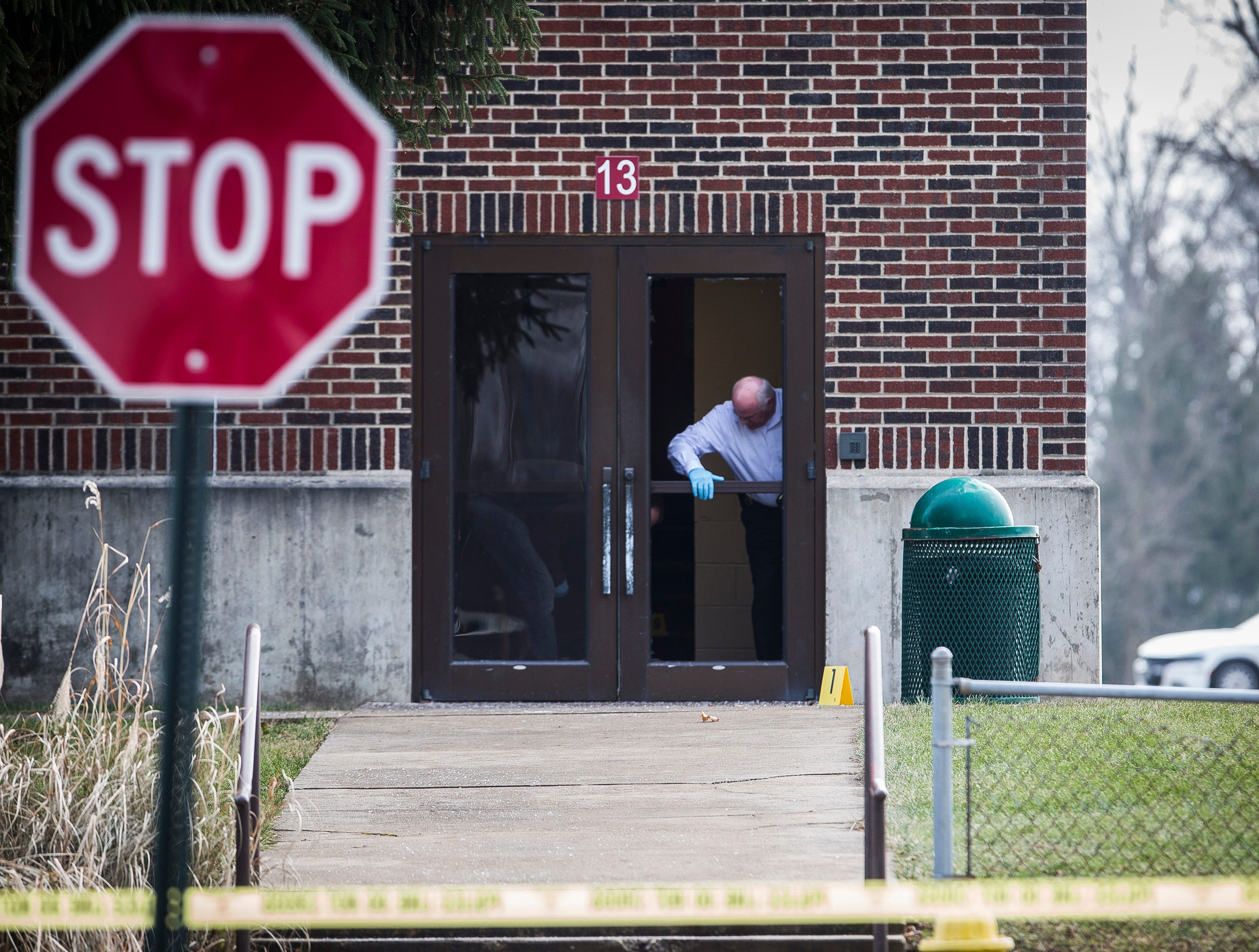 Investigators examine a a door  at Dennis Intermediate School where a shooter allegedly broke the glass to enter the building Thursday morning.